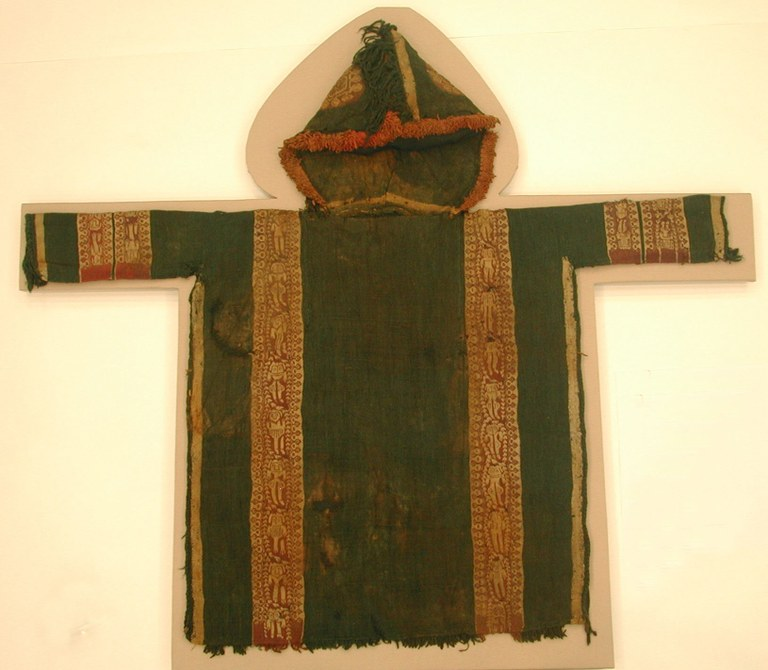 Tapestry weave of dyed wools, plain (tabby) weave ground of dyed wool, fringe of dyed wools along edge of hood and lower edge of tunic, L. 101 cm; W. 89 cm. Egypt, ca. 5th–7th century CE. The Metropolitan Museum of Art, Gift of George D. Pratt, New York, 1927 (27.239). This is a typical hooded tunic intended for a child, on which charms were placed to protect the child from the elements and unseen dangers. The medallions on the hood of the tunic, for instance, are composed of concentric circles, a motif intended to repel the evil eye among other perils.