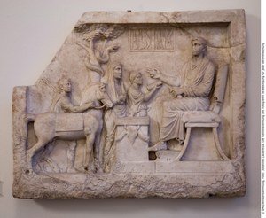 image showing a section of marble carved into a relief, depicting a seated male figure, three standing figures, a horse, a snake in a tree, and a box of surgical instruments
