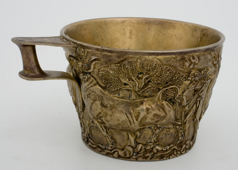 Photograph of a copper alloyed cup with a tiny handle and a raised relief design of a bull