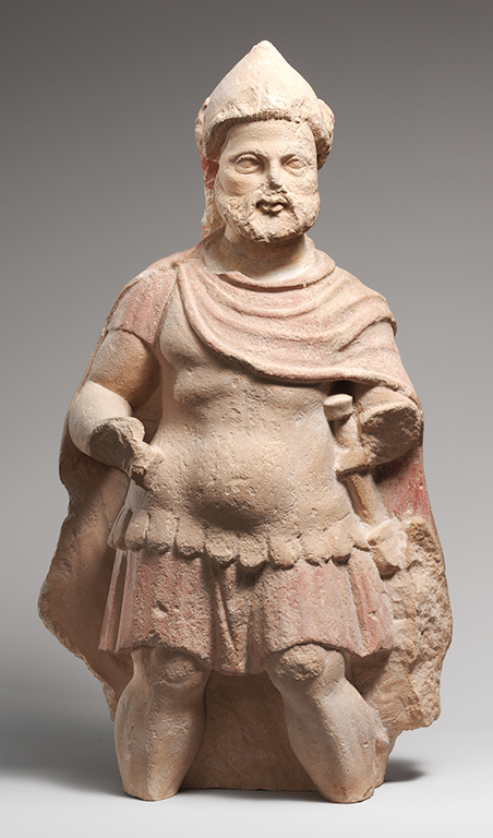 An image of the statue of a bearded male warrior with a hat made from sand-colored limestone.