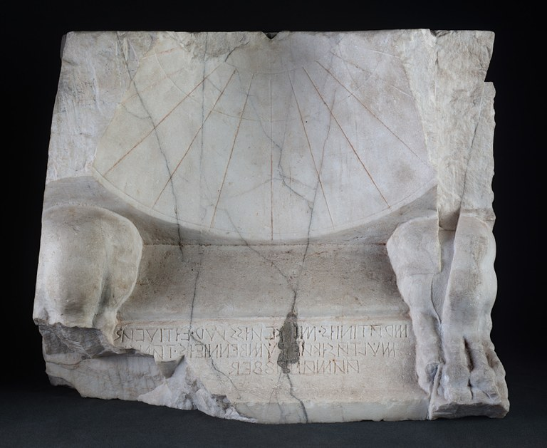 Image of a part of a marble sundial with Oscan inscriptions at the bottom. The sundial is conical, slightly chipped off along the edges and broken at the corners. There are animal legs (knee to toe) on the left and right sides of the inscription.