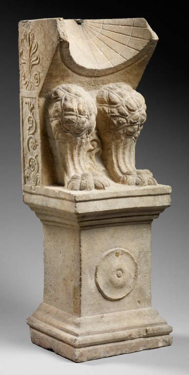 Image of a marble statue on a pedestal with a conical sundial and an animal's front legs (knee to toe)