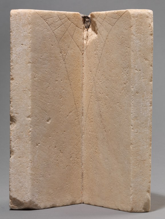 Two rectangular slabs of white marble placed adjacent to each other with inscribed lines at the top center, making a vertical sundial.