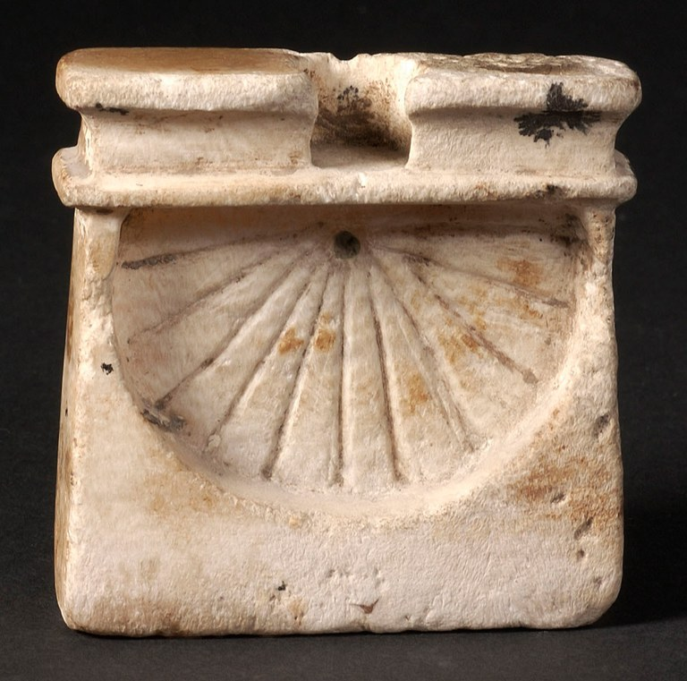 A Egyptian mini vertical sundial created in alabaster. The sundial has an inverted fan appearance with inscribed lines.