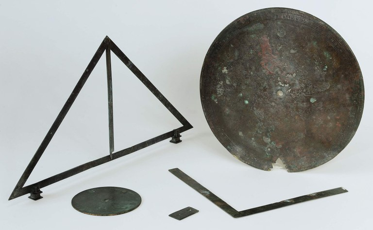 Image of a set of five geometrical and measuring instruments made out of bronze and shaped like disks, a triangle, a right angle, and a small rectangle.