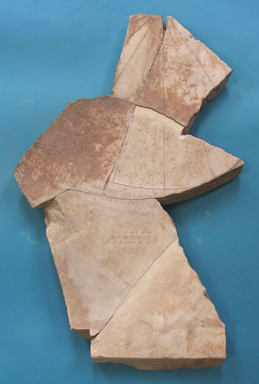 Image of the fragments of an equatorial sundial with Greek inscription, made out of marble. Six pieces are reassembled in an irregular shape with chipped edges.