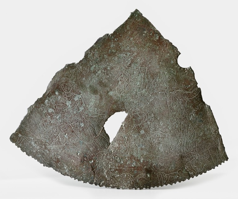 Image of a irregularly triangular fragment of a bronze dial plate with constellation-resembling human forms inscribed on it.