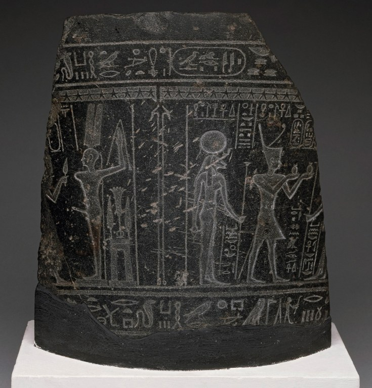 Image of a fragment of a black basalt slate with inscribed Egyptian figures in profile on it and hieroglyphic writing along the top and bottom of the image. One male figure has an erection.