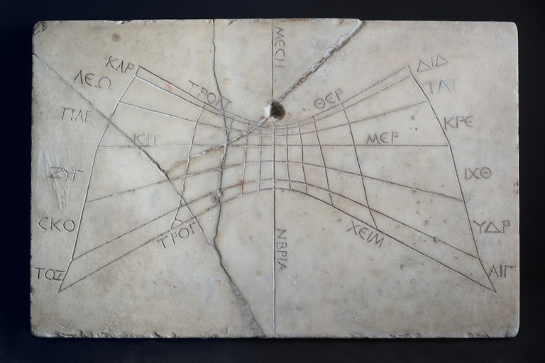 Image of rectangular marble horizontal sundial with a grid-like pattern and inscribed Greek labels on it.