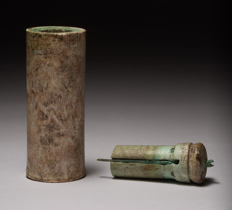 Image of a portable cylindrical sundial made from bone. The sundial has two parts: the hollow cylinder and an insertable plug housing the gnomon, which can be rotated to project at a right angle to the cylinder for use or be contained within it for storage.