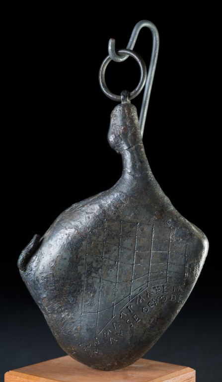 Image of a portable bronze sundial that is shaped like a ham. The sundial is suspended from a metal mount for exhibition.