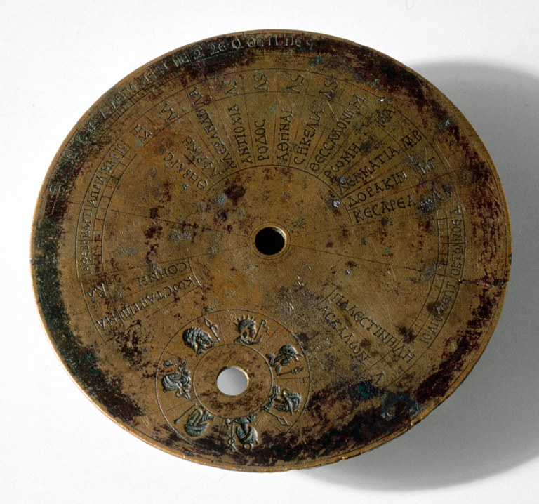 Image of a portable universal brass circular sundial: a disk inscribed with concentric and radiating lines, Greek labels, and figures of human heads.