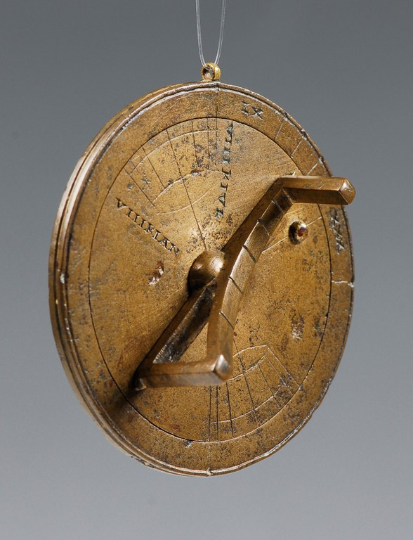 Image of a portable universal bronze circular sundial with concentric and radiating lines inscribed on one face and labeled with Roman numerals. A gnomon of the same material projects above and along the plane of the circular plate.