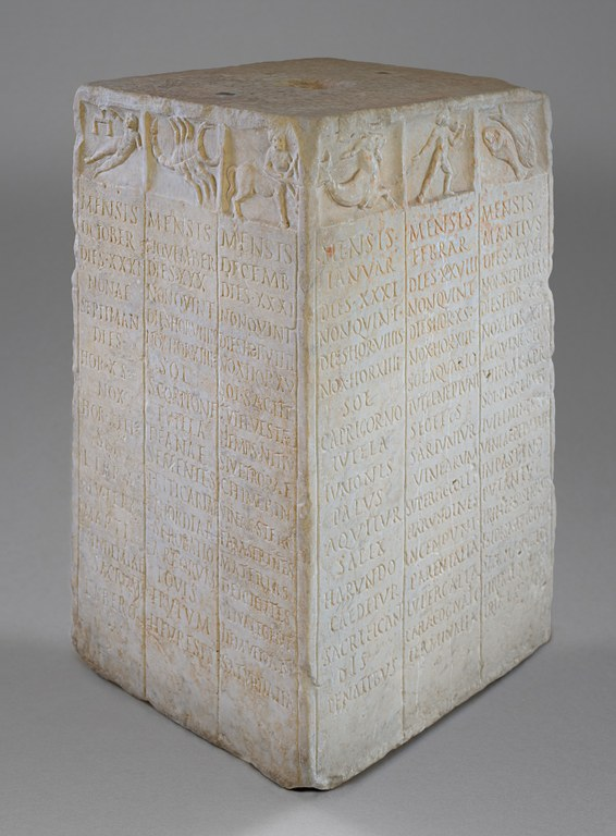 A marble block with three columns of Latin text engraved per per side and images of the zodiac on the top.