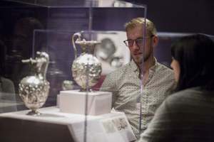 Two students look at silver vessels in display case