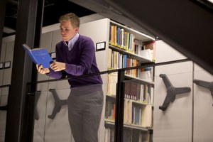 Student reads book in stacks of library