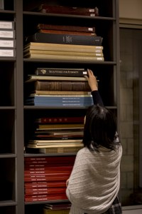 Student reaches for folio book in library stacks
