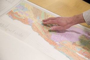 Hand pointing out location on map in folio volume