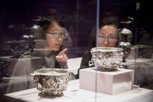 Two students discuss silver cups in display case