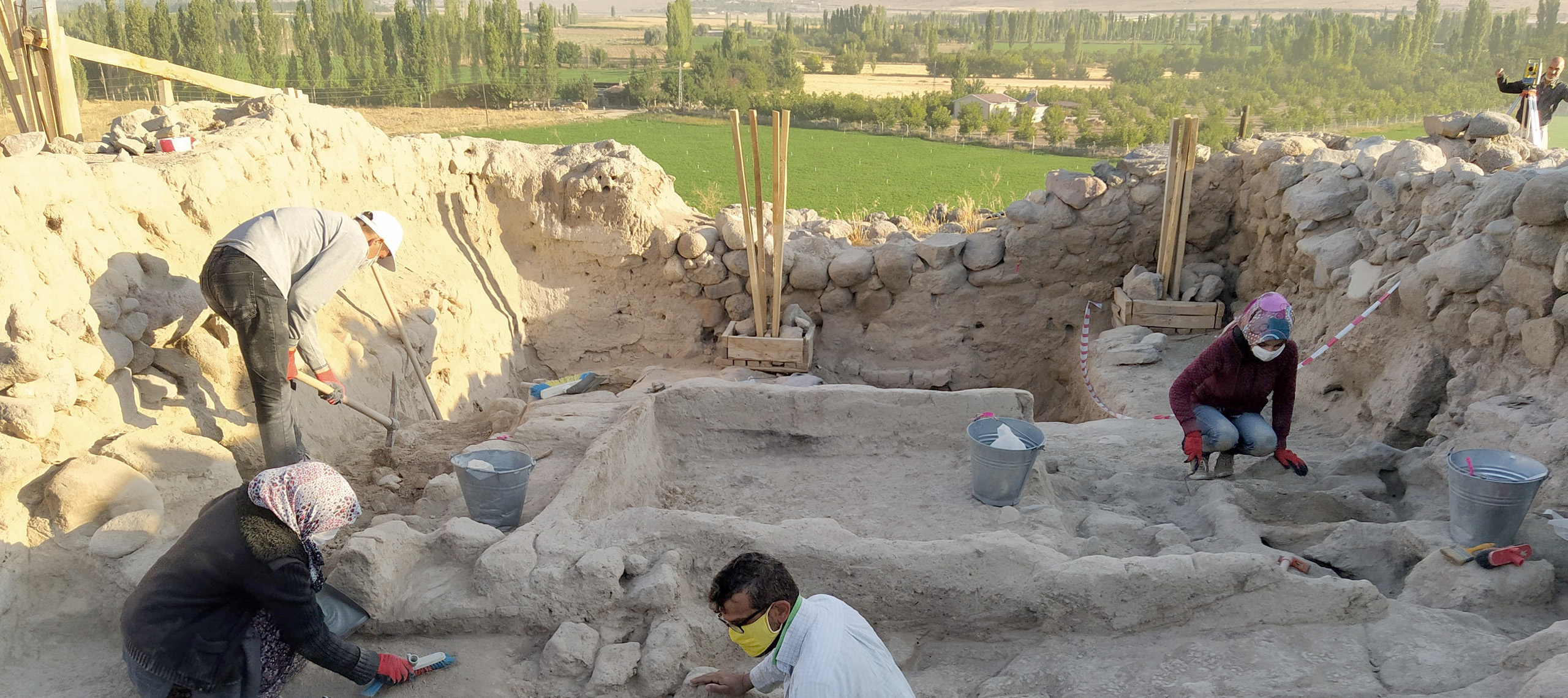 Four individuals wearing masks, long sleeved shirts, and long pants work in an excavation with partially exposed walls of stone and mud or plaster. There is a large rectangular shallow feature in the middle of the area and a man with a total station can be seen beyond the wall. Behind him a green agricultural area bounded by trees can be seen
