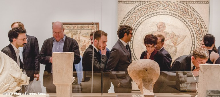 A group of people examine ancient artifacts in a large gallery display. Large mosaics in frames are mounted on the walls behind them.