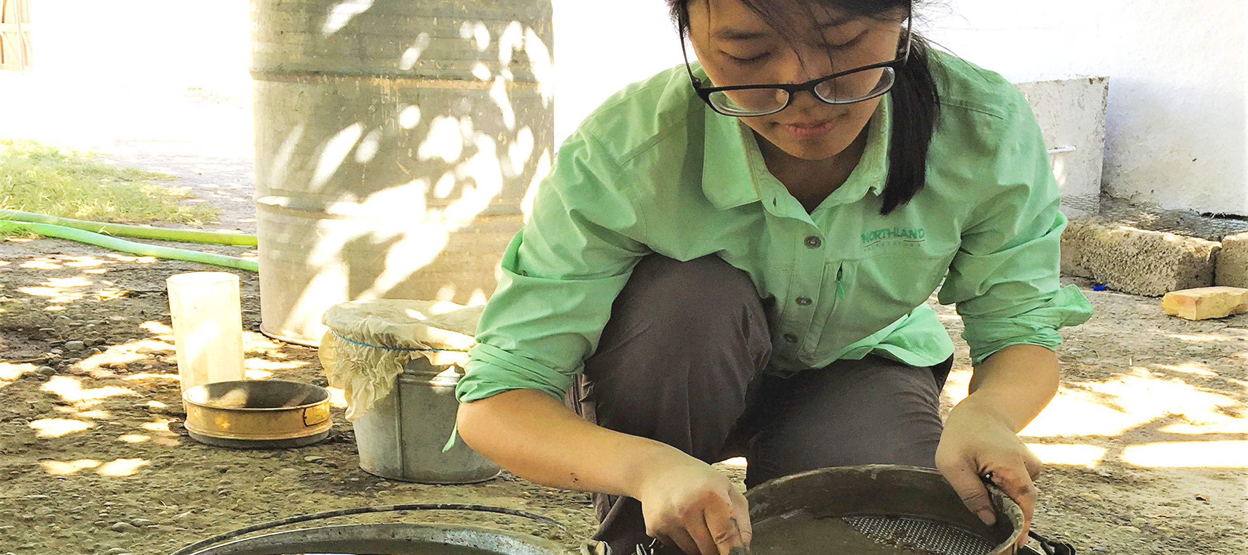 A woman in a green shirt and gray slacks with glasses kneels and works wet soil through a round pan with a mesh base.
