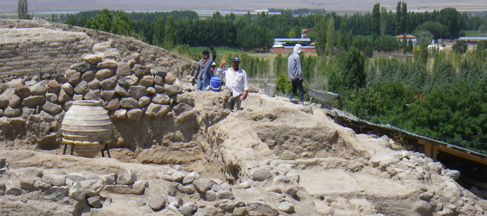 Image of an active dig site, with some of the workers waving