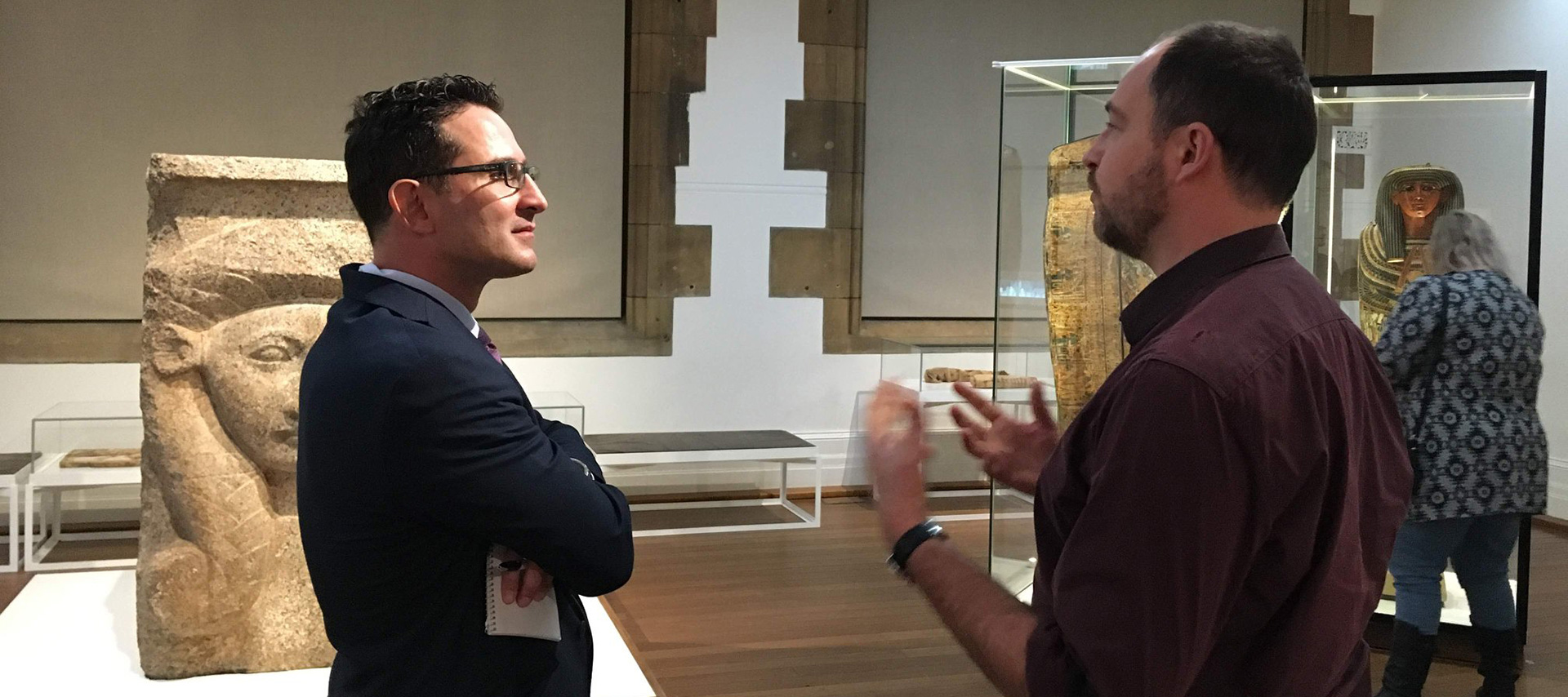 Image of Antonis Kotsonas listening to an unidentified man in a museum, amidst Egyptian materials