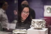 Woman looking at silver object in display case