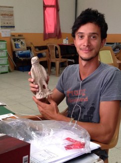 Student with the bird of prey statue in the dig house