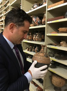 Professor Kotsonas holding and examining a vase in the storage collections of the Nicholson Museum
