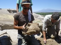 Group of three workers at archaeological site with mountain in background.
