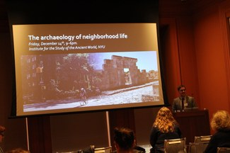 "Andrew Dufton introduces a session in front of a screen that reads ""the archaeology of neighborhood life"""