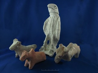Photograph of a stone statue of a hawk, together with three other stone or ceramic objects that appear to be cattle.