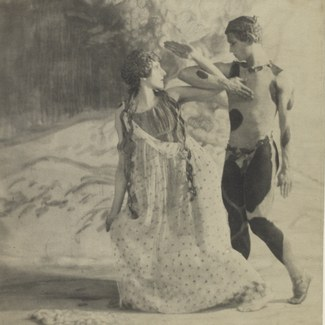 A vintage photograph in black and white depicting two dancers in costume with their arms intertwined