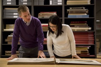 Two students look at a folio volume in the ISAW Library.