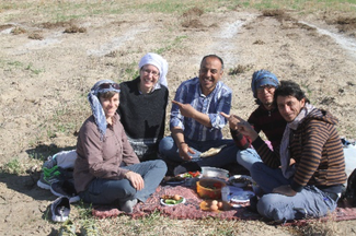 Five people sitting on a blanket in a field eating from portable containers.