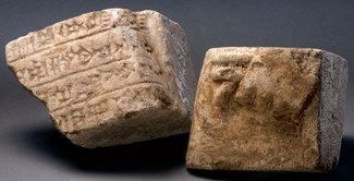 Photograph with two roughly cube-shaped pieces of fragmentary bricks. One piece has cuneiform inscriptions with straight lines between the rows of symbols and the other shows the top of a closed hand in relief. Both bricks are a brownish color.