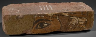 A rectangular brick with a part of a god's face on the face of the brick. The eye and ear are prominent. The brick is light brown with hints of black, white, and light green pigment