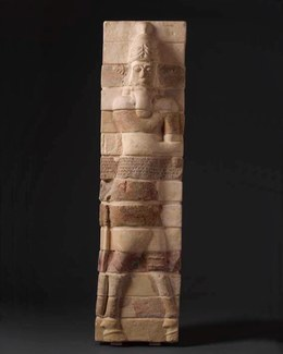 Rectangular pillar with bricks in molded relief showing a man with a long beard and a tall hat, as well as bull-like hooves for legs. The whole figure is divided into 14 stacked horizontal bricks and the brick at the mid section has a cuneiform inscriptio