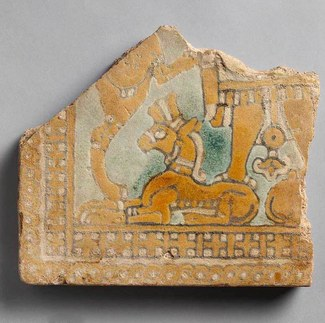 Fragmentary tile with a genie standing on a bull. The tile is orangish- yellow in color