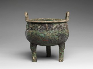 Bronze footed vessel with handles and a decorated band near rim.