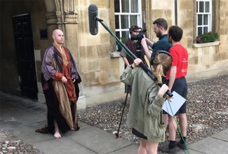 A behind the scenes shot of the actors in costume and the film crew