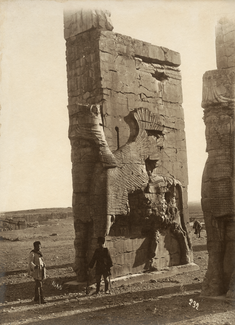 A sepia-tone photograph shows two men standing next to a free-standing rectangular stone wall more than 6 times their height. A winged bull with humanoid head bearing a crown is carved in relief on the monument. Another such monument can be partly seen at right.