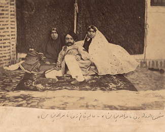 In a sepia-toned photo, a man and two women recline on a carpeted floor. Persian writing has been added to the margin below the photo.