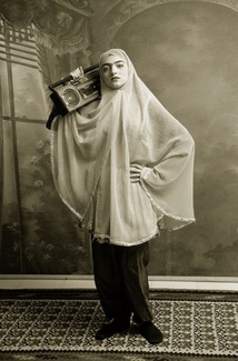 A woman wearing a hijab and leggings stands on a rug in front of painting of an interior space. She has her left hand on her hip and, with her right hand, holds a portable stereo cassette radio propped on her right shoulder.