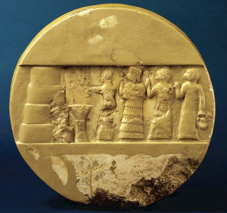 On a smooth, circular stone or ceramic object, a rectangular band across the middle shows four human figures lined up in front of altar and an object made of four large rounded blocks stacked, each slightly smaller than the one below. The disc is damaged at the bottom and in the figural area. It is coated with a yellow pigment or glaze, which has worn off in some areas.