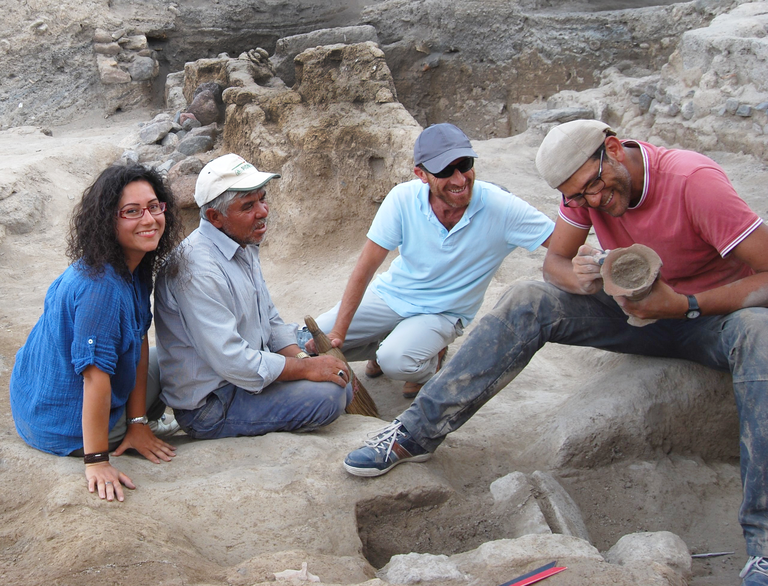 Four people sit in the middle of a partially excavated area. Portions of walls and stone structural components can be seen. One individual holds a hand broom. Another holds and leans over a cylindrical ceramic object with dirt still inside it.