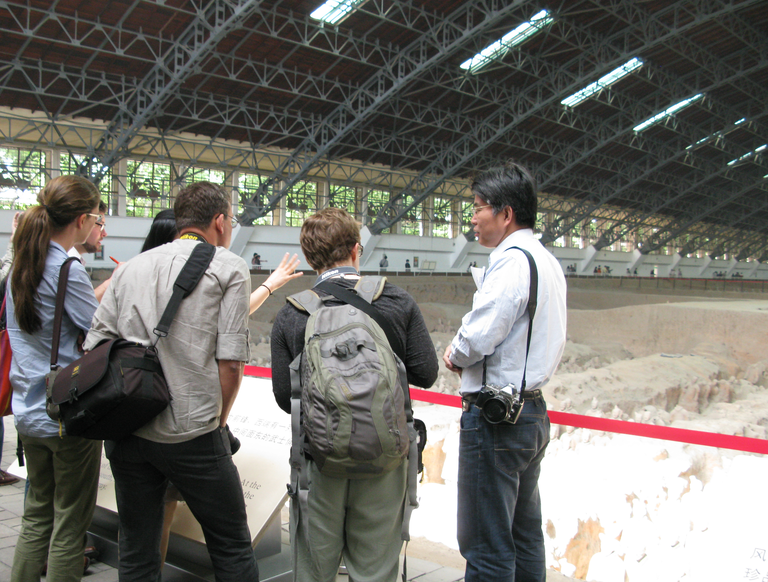 A group of people with backpacks and cameras are photographed from behind. They stand at a glass retaining wall in front of an excavated pit of ceramic warrior statues. The arched protective roof over the excavated area is also clearly visible. Photo courtesy of Lillian Tseng.