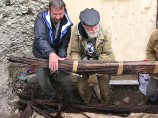 Two men grasp and lift a large wooden beam that extends out of the photo to the right. They appear to be in an excavated trench. Both are wearing warm outer garments.